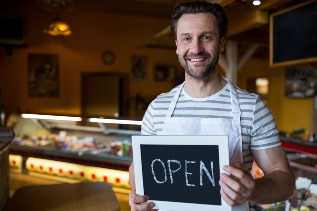 Portrait of smiling owner holding a open sign in the bakery shop