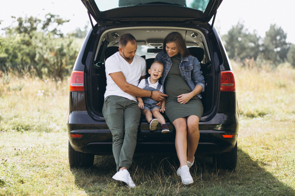 Husband with pregnant wife and their son sitting in car