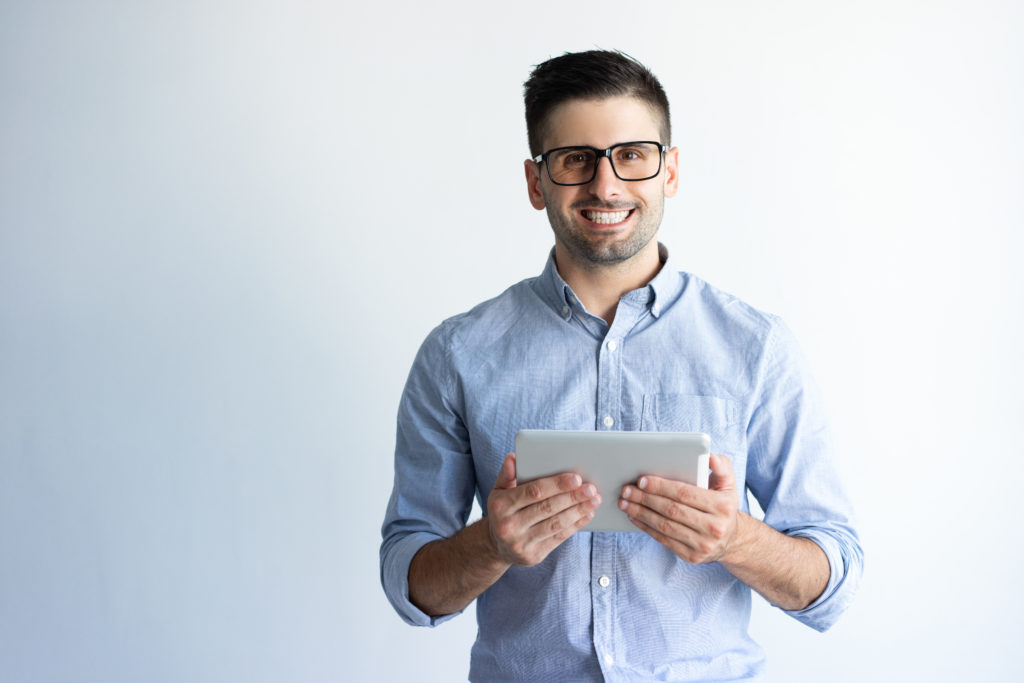 Happy male holding tablet.