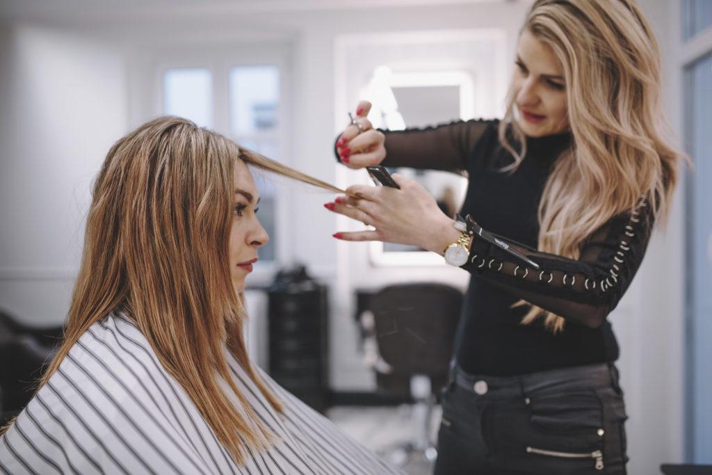 Hairstylist cutting hair in her salon.