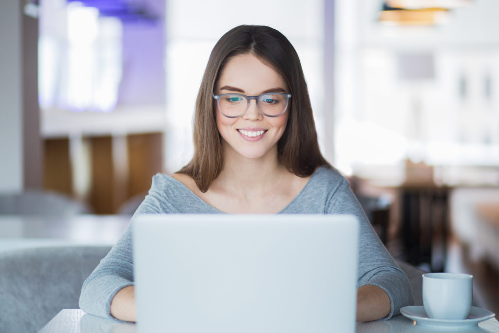Portrait of cheerful student using laptop in cafe