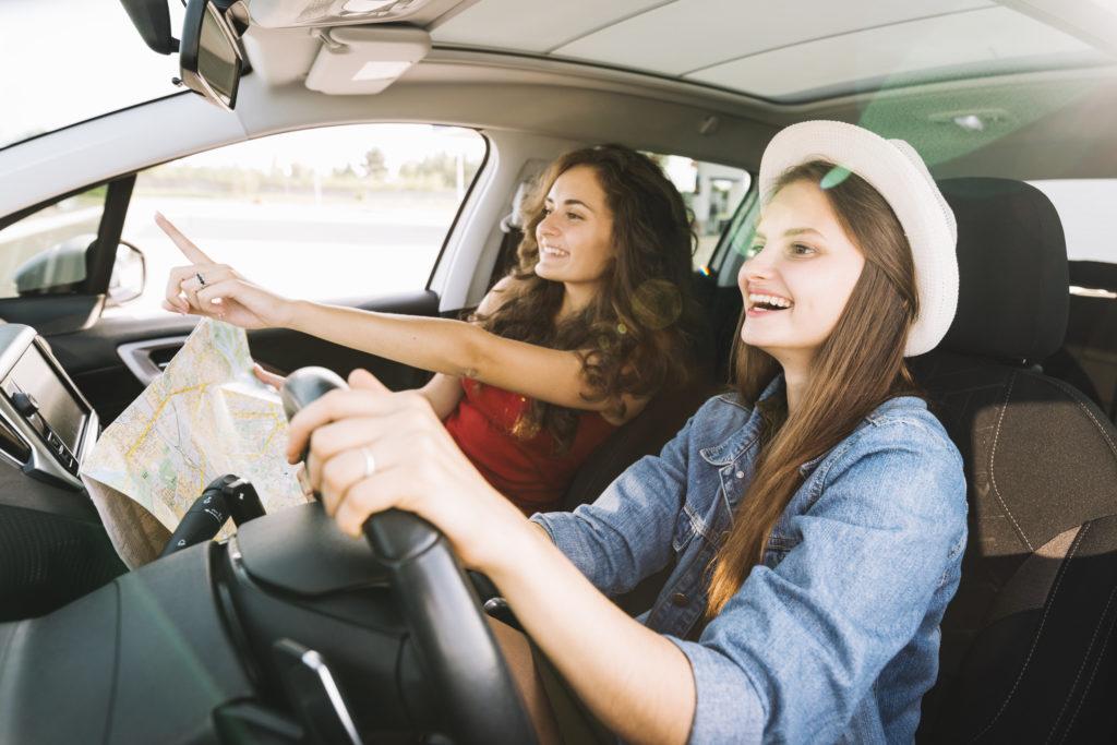 Females driving car on road trip.